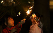 two smiling twins Asian girls playing sparkler. they wear traditional clothing cheongsam. background for Chinese New Year.