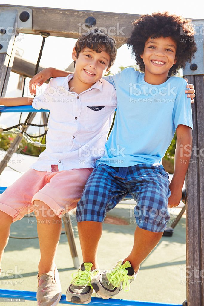 Two smiling boys sitting on playground equipment stock photo
