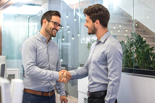 istock Two smiling business men shaking hands together after successful meeting. 865432310