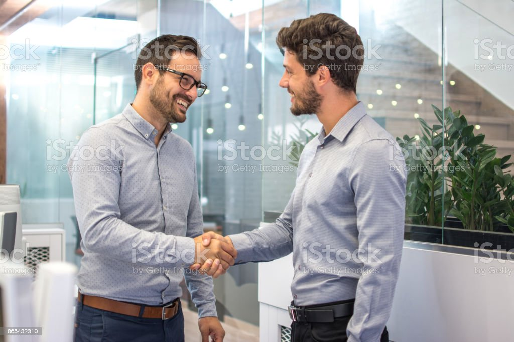 Two smiling business men shaking hands together after successful meeting. stock photo