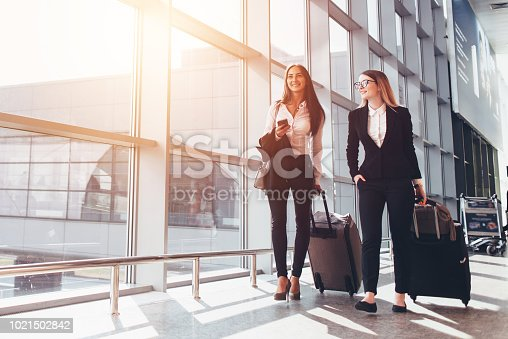 Two smiling business partners going on business trip carrying suitcases while walking through airport passageway.