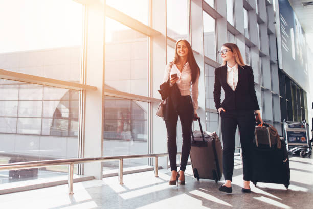 two smiling business partners going on business trip carrying suitcases while walking through airport passageway - airport stock photos and pictures