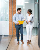 istock Two smiling business people walking through office hall and talking. 925689578