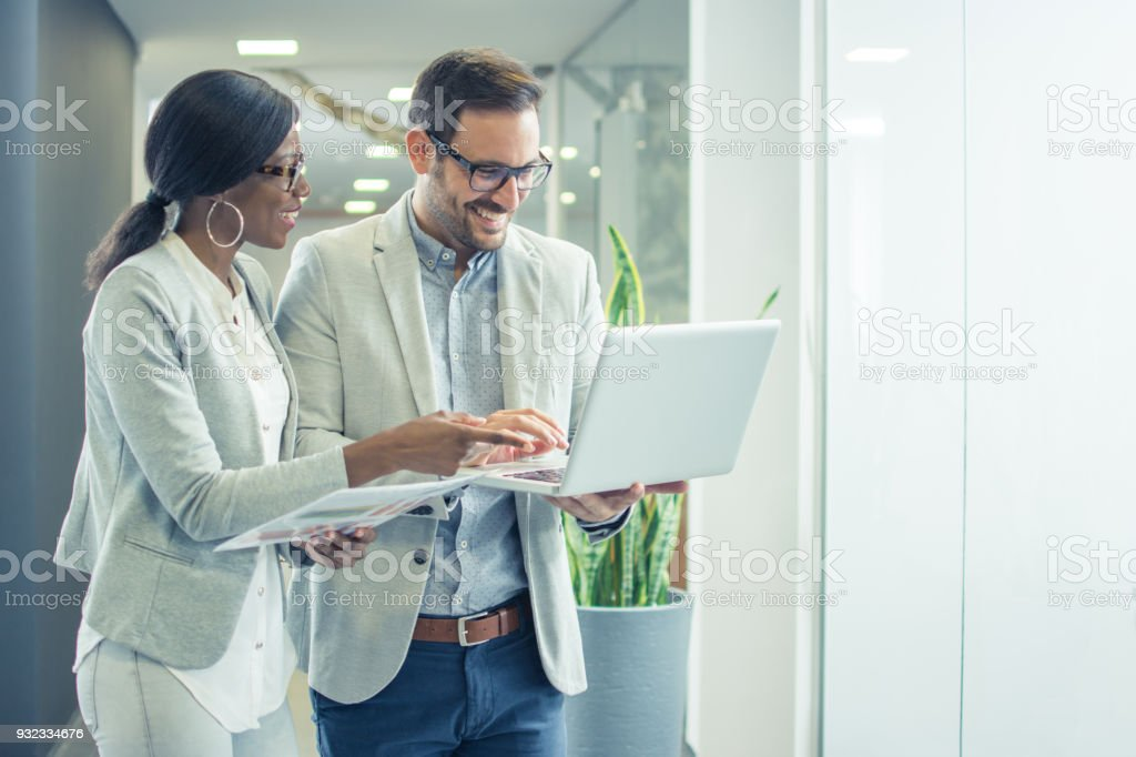 Two smiling business people with laptop discussing about new project...