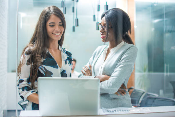 Two smiling business women using laptop in office stock photo