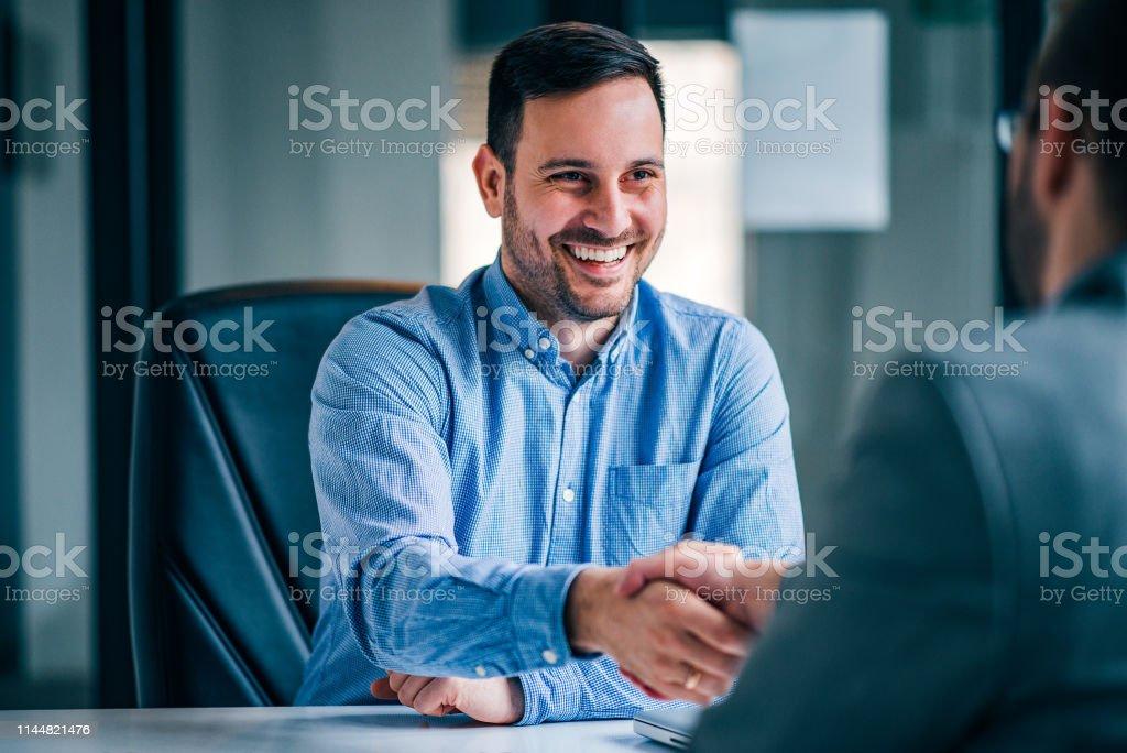 Dos hombres de negocios sonriendo estrechándose la mano mientras estaban sentados en el escritorio de la oficina. - Foto de stock de Acuerdo libre de derechos