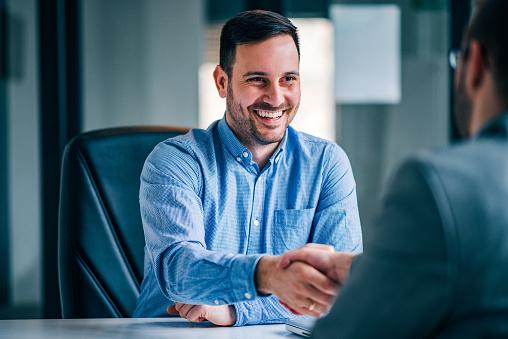Dos Hombres De Negocios Sonriendo Estrechándose La Mano Mientras Estaban Sentados En El Escritorio De La Oficina Foto de stock y más banco de imágenes de Acuerdo