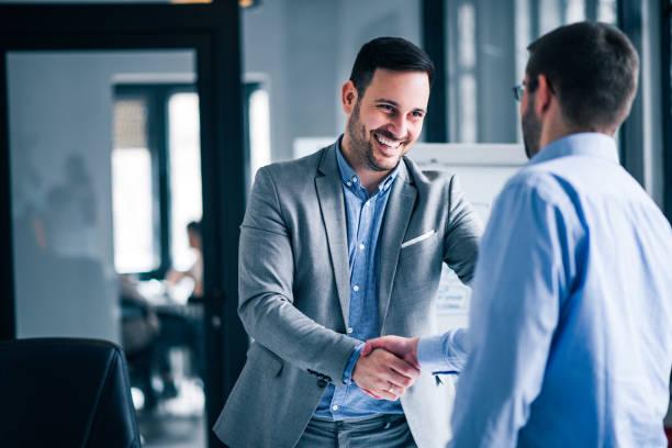 dois homens de negócios de sorriso que agitam as mãos ao estar em um escritório. - business man - fotografias e filmes do acervo