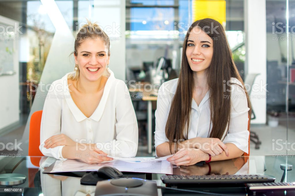 Two smiling businesswomen sitting in the office and looking at camera. stock photo