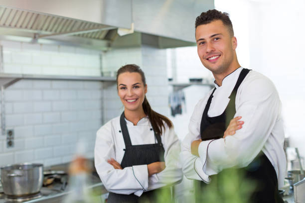 Two smiling chefs in kitchen Two smiling chefs in kitchen chef's whites stock pictures, royalty-free photos & images