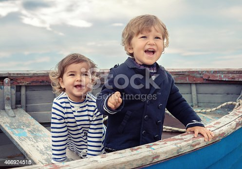 istock Two smiling children playing in a worn rowboat 466924518