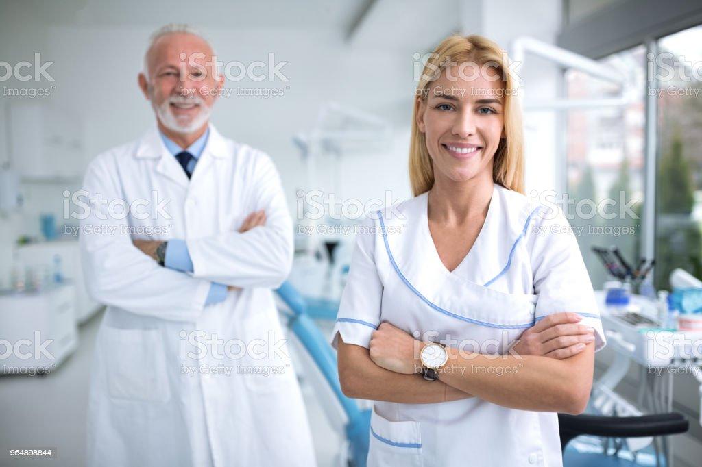 牙醫辦公室裡的兩個微笑牙醫 - 免版稅一個人圖庫照片