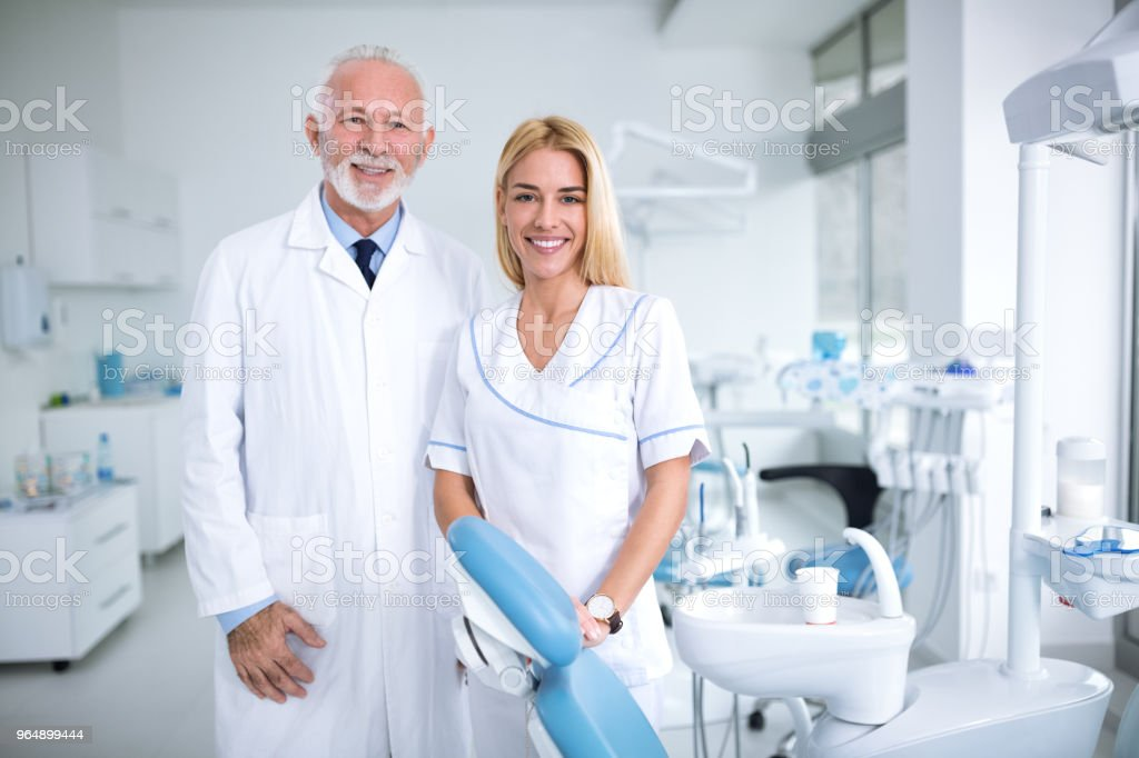 Two smiling dentists in a dental office royalty-free stock photo