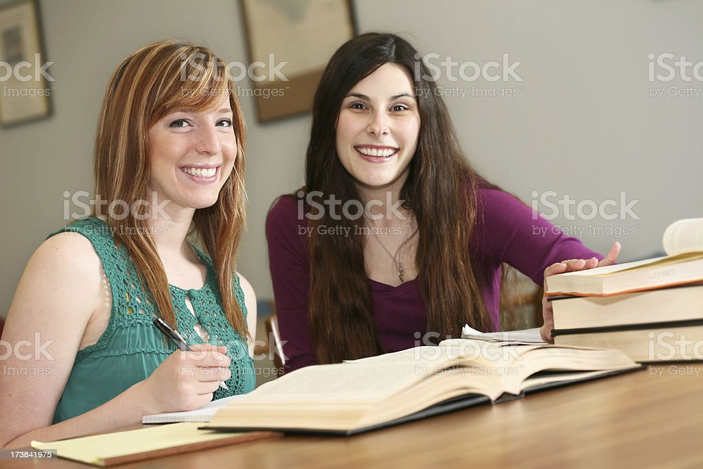 Two Smiling Female College Students Studying in a Library royalty-free stock photo