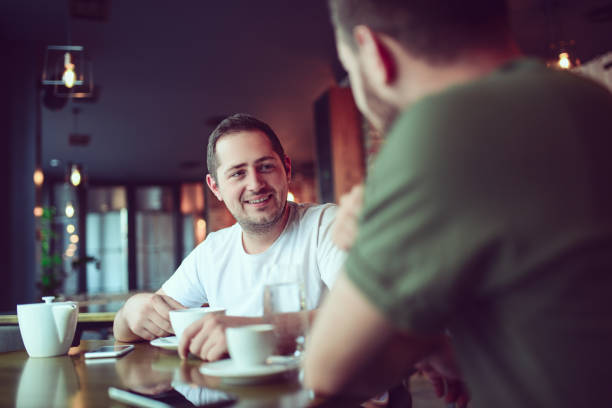 Two Smiling Friends Drinking Coffee and Socialising in a Cafe stock photo