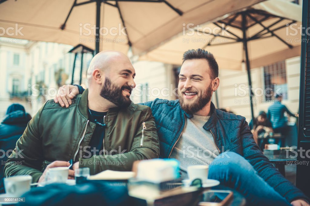 Two Smiling Friends Drinking Coffee and Talking in Coffee Shop stock photo