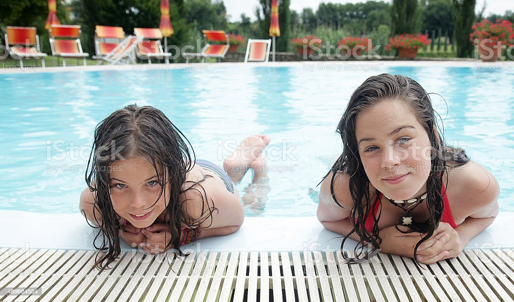 Two smiling girl in the swimming pool stock photo