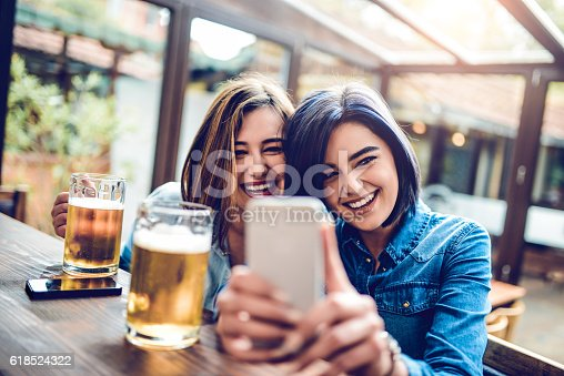Two smiling fashionable young women how sitting at bar restaurant, drinking beer and taking selfie with their mobile smartphone.