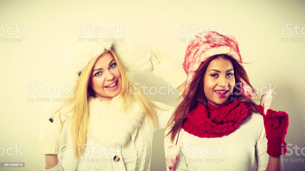 Two smiling girls in warm winter clothing. stock photo