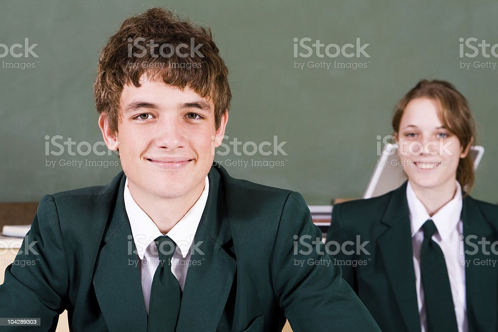 Two smiling high school students in classroom stock photo