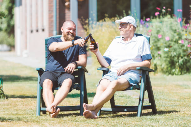 Two smiling men (young and old) drinking beer in the summer garden - best friends (father and son) toasting and laughing together - family and Father's Day celebration concept