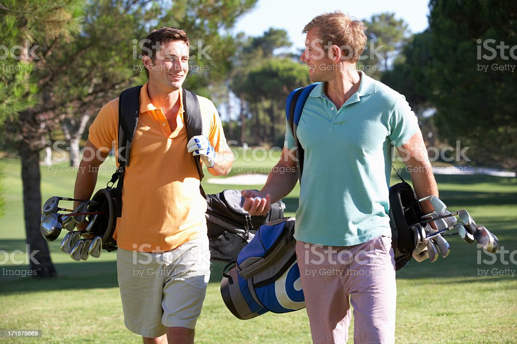 Two smiling men with golf gear on a course stock photo