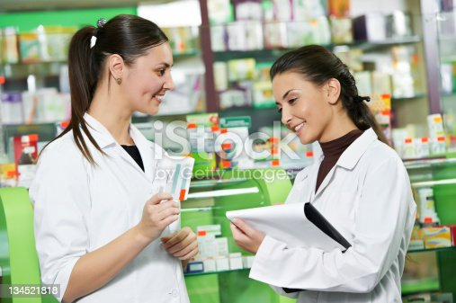 istock Two smiling pharmacists working in the drugstore 134521818