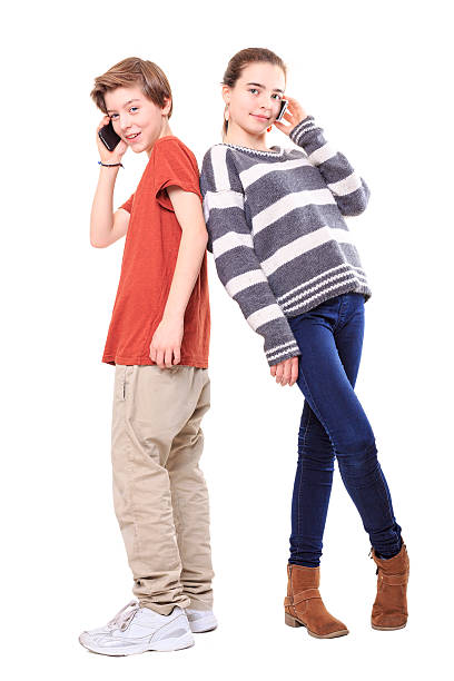 two smiling teenager with their mobile phones stock photo
