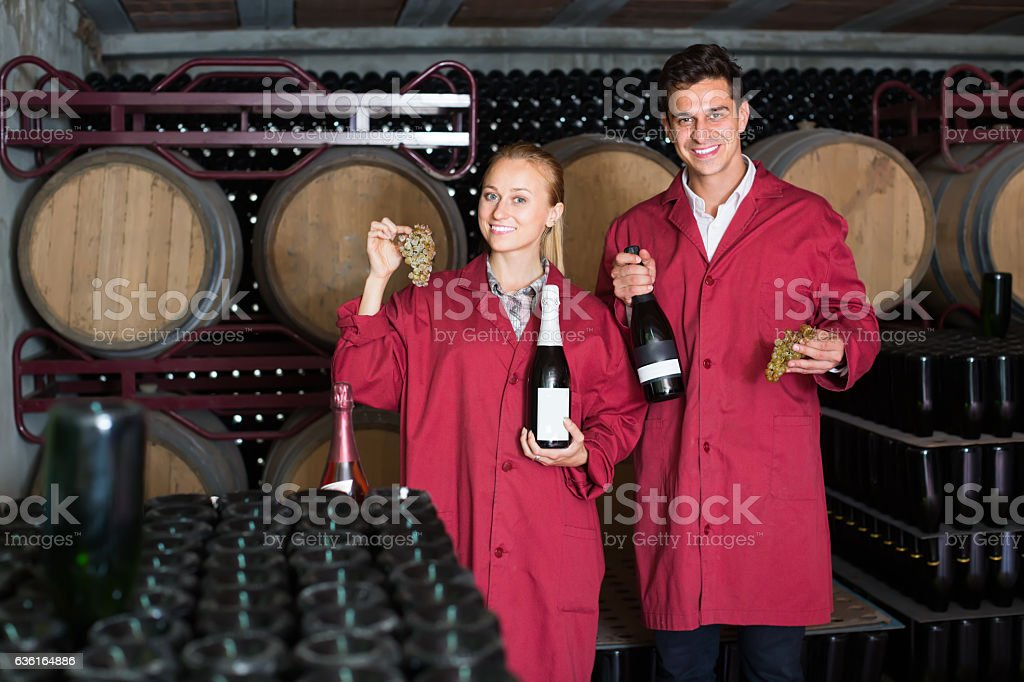 Two smiling winery employees in aging section in cellar stock photo