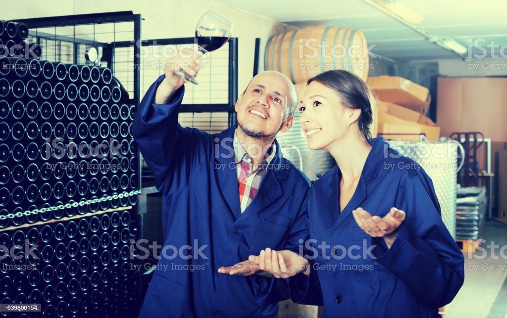 Two smiling winery workers different ages in aging section stock photo