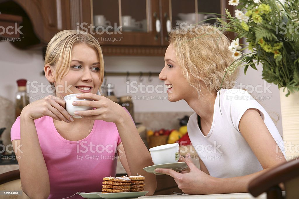 Two smiling woman having tea and cookies royalty-free stock photo