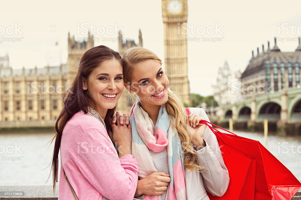 Two smiling women at Westminster Bridge, London A portrait of two young women, smiling brightly and looking directly at the camera.  The Westminster Bridge is in the background.  The woman on the left is a brunette, wearing a pink sweatshirt while the woman on the right is a blond who has a pink and light-blue scarf on her neck and a red bag on her shoulder. 20-24 Years Stock Photo