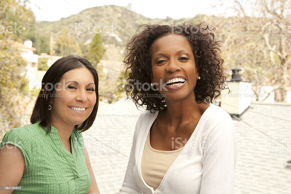 Two smiling women enjoying each other's company outdoors stock photo