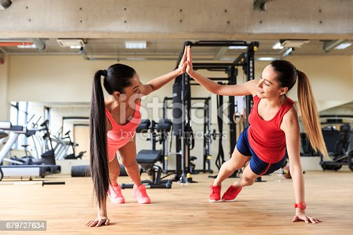 istock Two smiling women practicing in gym together 679727634