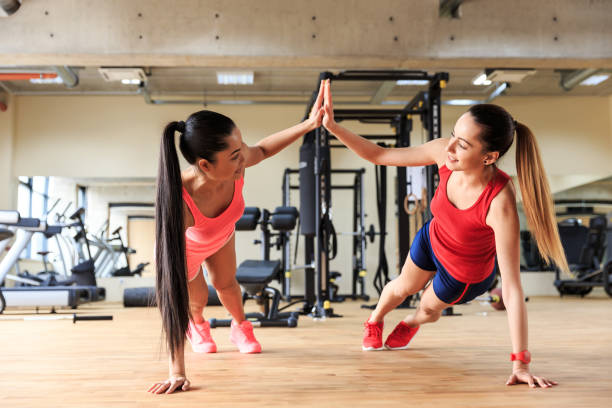 Two smiling women practicing in gym together stock photo