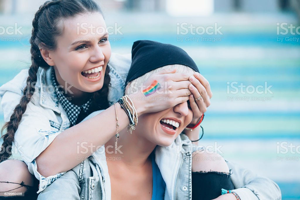 Two smiling women sitting on colorful stairs and having fun - Photo