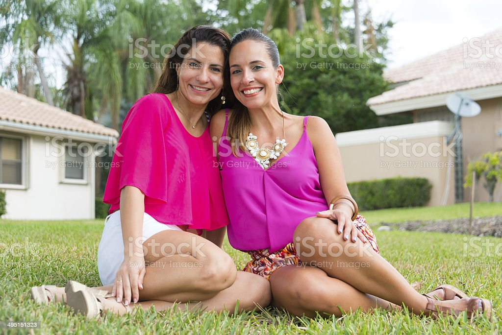 Two smiling women sitting on grass outside residence. stock photo