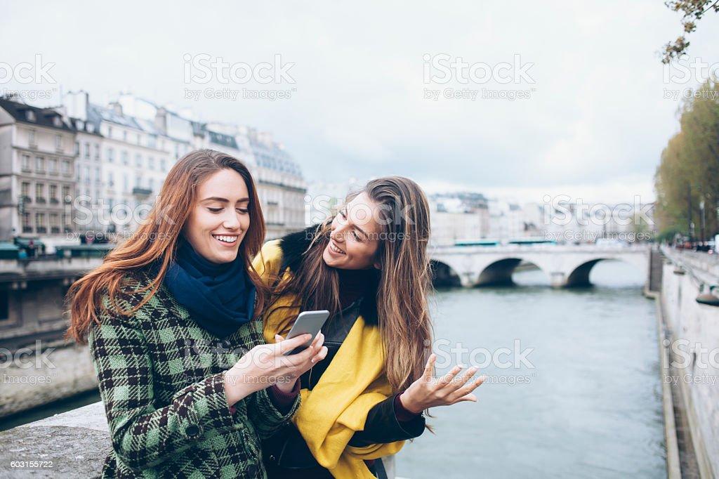 Two smiling women walking on bridge stock photo
