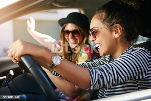 832085296 istock photo Two smiling young friends driving on a road trip together 832085206
