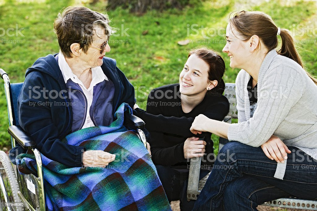 Two smiling young women chat to old woman in wheelchair royalty-free stock photo