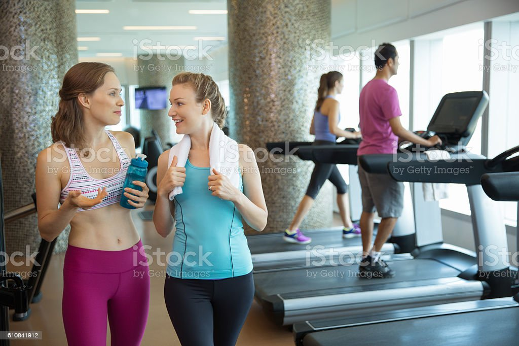 Two smiling young women chatting in gym stock photo