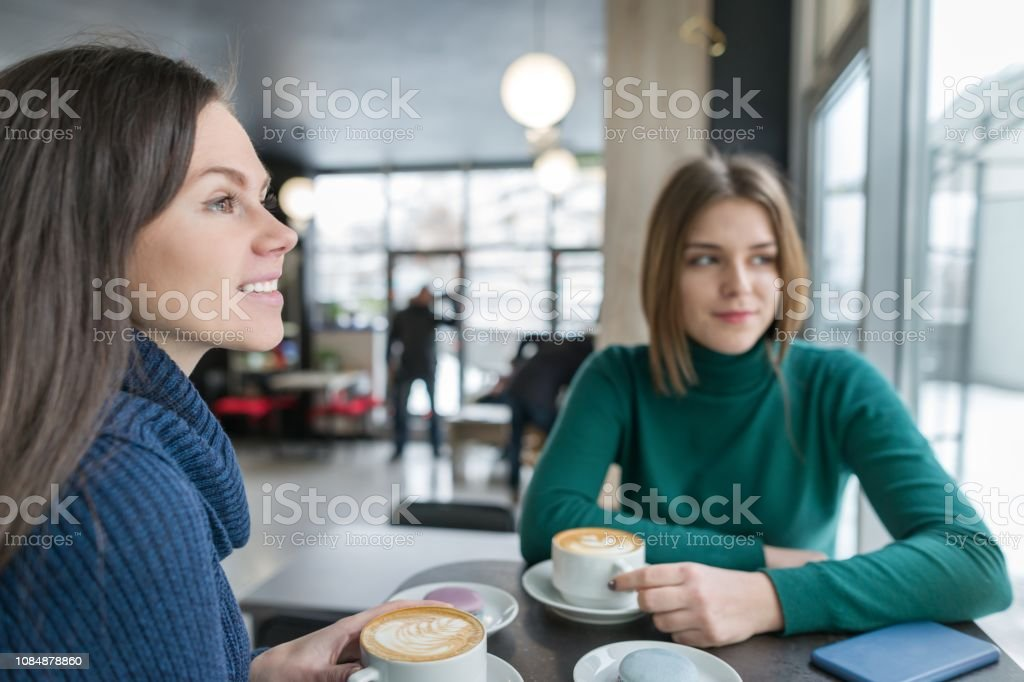Two smiling young women in coffee shop with coffee art and macaroons...