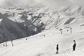 Two snowboarders descend on snowy ski slope and gondola lift at sun cloudy day. Georgia, region Gudauri. Caucasus Mountains in winter. Black and white toned landscape.
