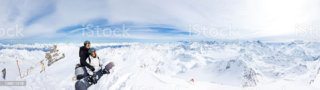 Two snowboarders on top of the mountain stock photo