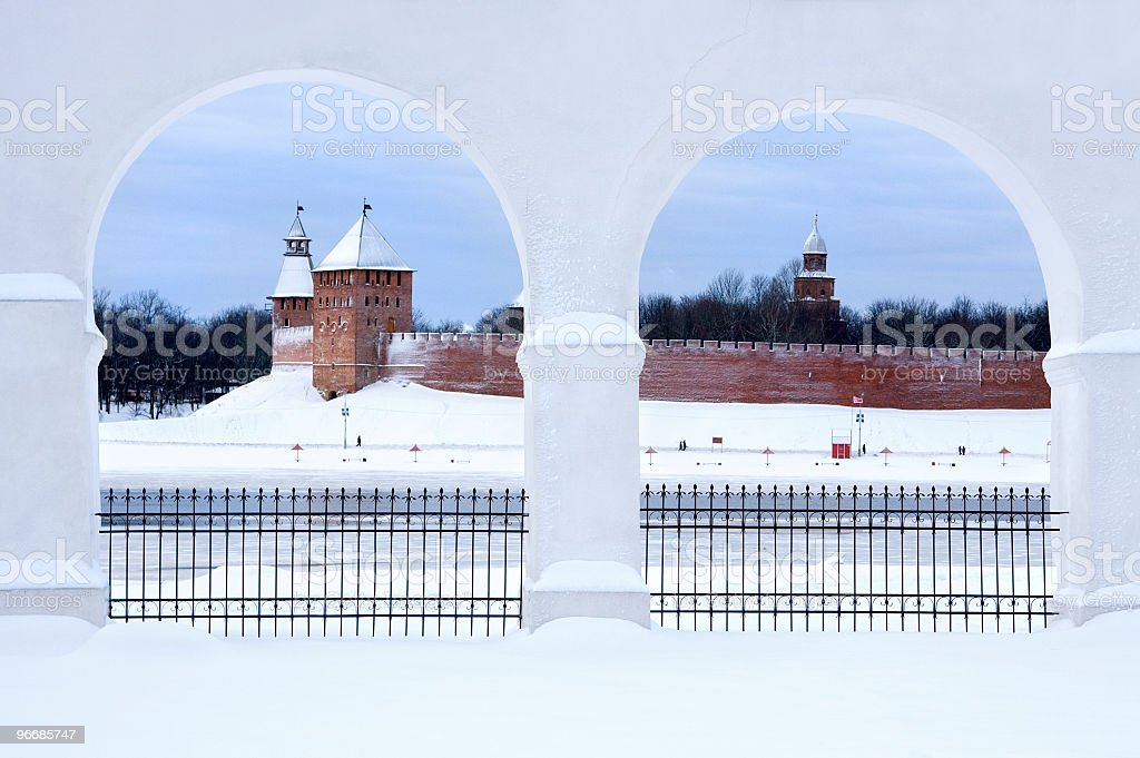 Two snow-white arches creates beautiful frame for ancient red castle stock photo