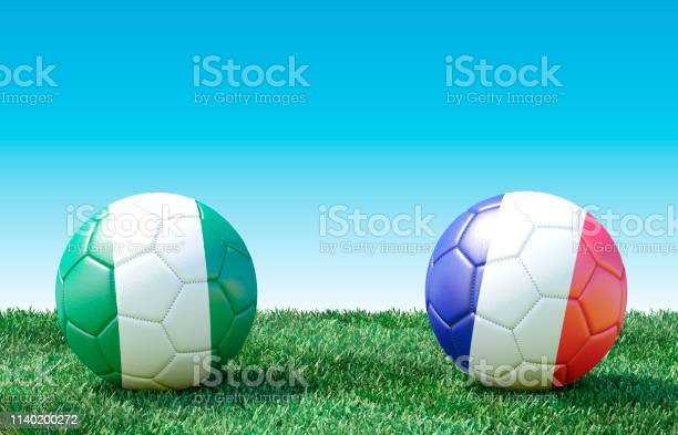 Two soccer balls in flags colors on green grass. Nigeria and France