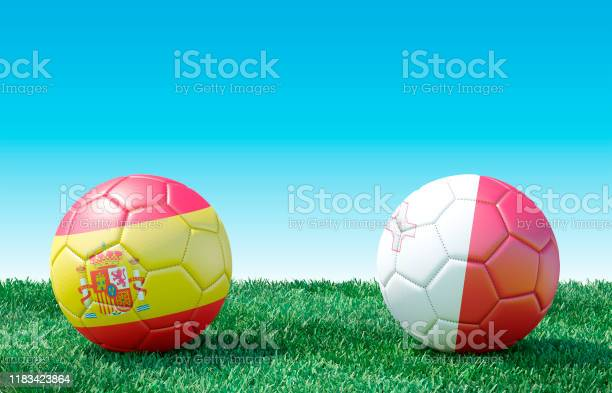 Two soccer balls in flags colors on green grass. Spain and Malta. Group F.