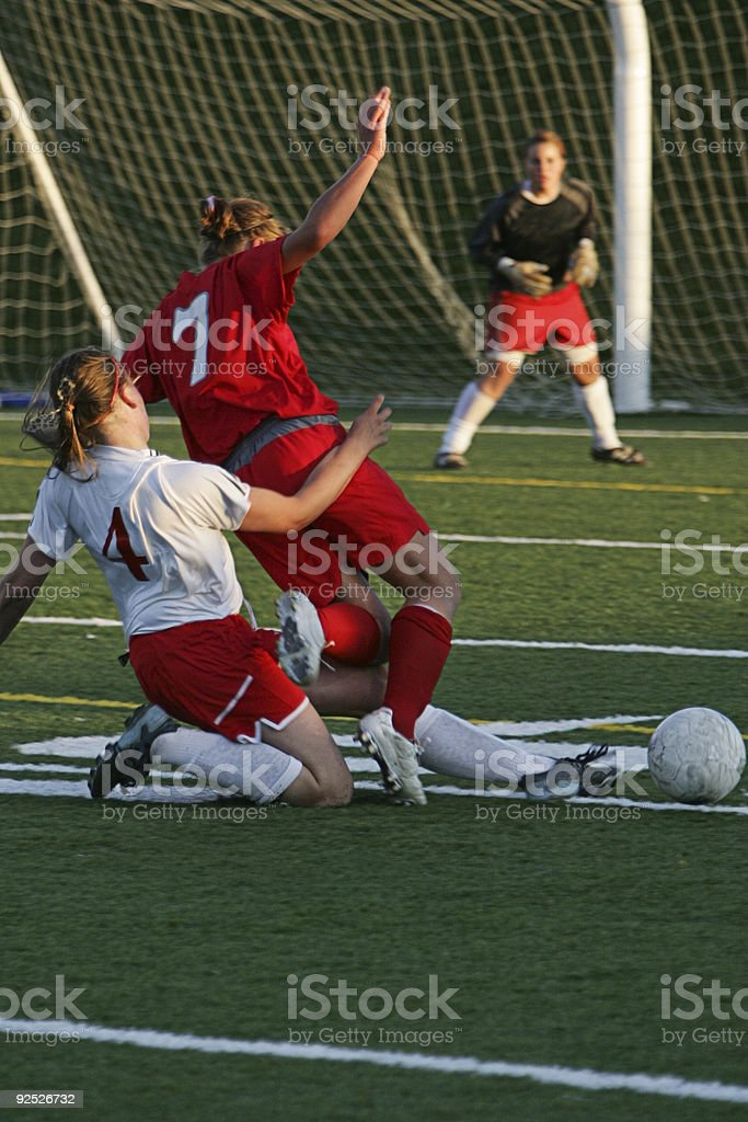 Two Soccer Midfielders Fight For Ball as Goalie Waits Anxiously royalty-free stock photo