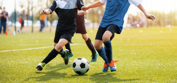 twee voetballers die een voetbal spelen en schoppen. benen van twee jonge voetballers op een wedstrijd. europese voetbal jeugdspeler benen in actie - internationale voetbal stockfoto's en -beelden