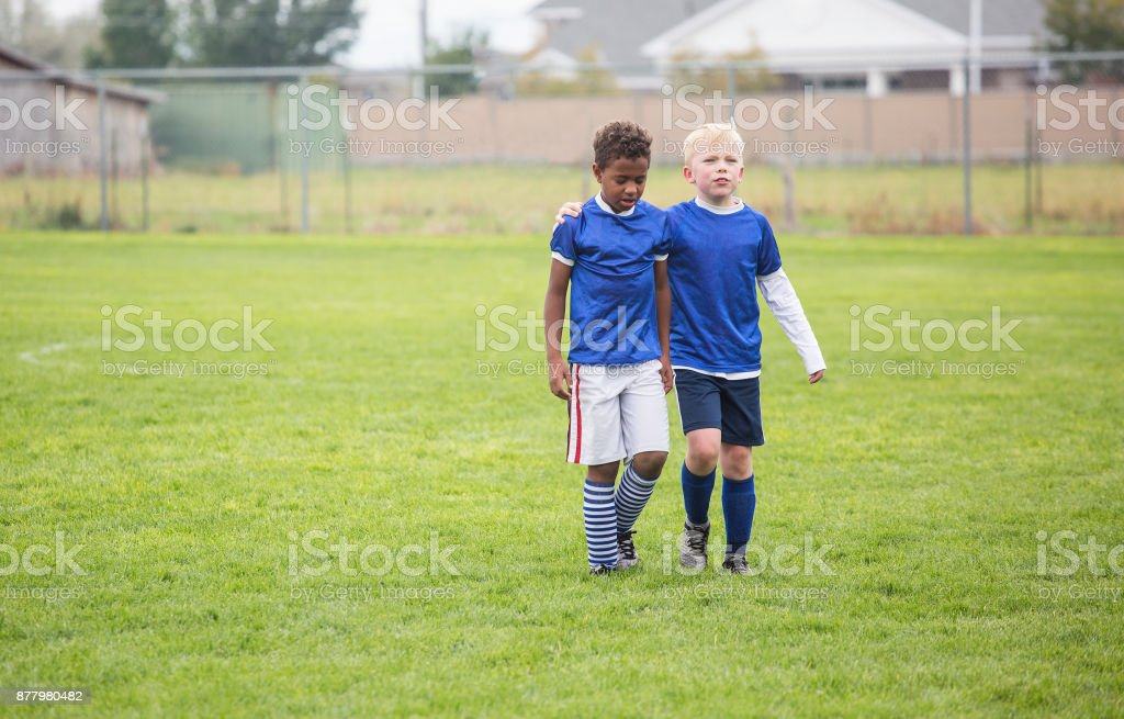 Two soccer teammates walking off the field after a loss stock photo